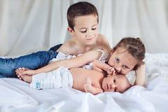 Geschwister mit ihrem neugeborenen Bruder Stockfotografie