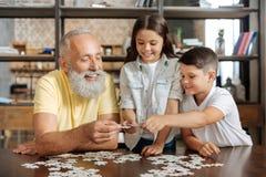 Geschwister und ihr Großvater, die drei Puzzlestücken sich anschließen stockfoto