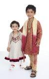 Geschwister zeigen traditionelle indische Kostüme an Lizenzfreie Stockfotos