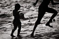Geschwisterbrüder, die das Fangen an einem Strand spielen stockfoto
