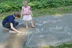 Geschwisterkinder, die Bürgersteigskreiden teilen und auf Asphaltoberfläche zeichnen Stockfotografie