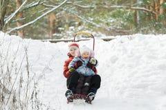 Geschwisterkinder, die den Spaß schiebt hinunter schneebedeckten Hügel während der Winterzeit haben Stockfoto
