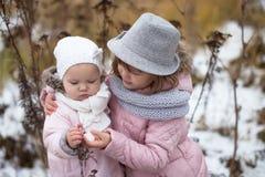 Geschwisterschwestermädchen im rosa Jacken- und Knitschal und im Fedora ha Stockfotos