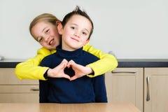 Geschwisterumarmung, die ein Herz mit der Hand bildet Stockfoto