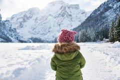 Gesehen von hinten Kind im grünen Mantel, der draußen spielt lizenzfreies stockfoto