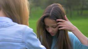 Geselliges junges Mädchen, das mit ihrer Freundin spricht und das Haar sich tut Haar kämmt Gefühlvergnügen und -lächeln stock video footage