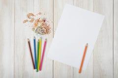 Gesetzte bunte Bleistifte mit der Hauptorange eine und verschiedene farbige Schnitzel auf einem Weilepapier Draufsicht der Design Lizenzfreies Stockbild