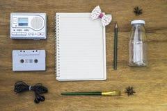 Gesetzte Draufsicht der Erholung mit leerem Papier und Kassettenrecorder Stockfotografie