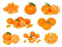 Gesetzte ganze und geschnittene Mandarinen mit den grünen Blättern (lokalisiert) Stockbild