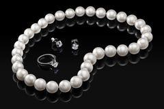 Gesetzte weiße Perlenhalskette und -schmuck des Luxus mit Diamanten im Ring und in den Ohrringen auf einem schwarzen Hintergrund  Stockbilder