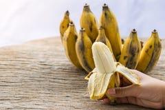 Gesetzter an Holztisch der Banane Schale stockfotos