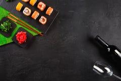 Gesetzter Sashimi der Sushi und Sushirollen, Flasche Wein und ein Glas gedient auf Steinschiefer stockfotografie