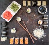 Gesetzter Sashimi und Rollen der Sushi auf einem dunklen Brett Hölzerner Hintergrund Beschneidungspfad eingeschlossen Stockbild