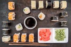 Gesetzter Sashimi und Rollen der Sushi auf einem dunklen Brett Hölzerner Hintergrund Beschneidungspfad eingeschlossen Lizenzfreie Stockbilder