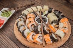 Gesetzter Sashimi und Rollen der Sushi auf einem hölzernen Brett Hintergrund Stockfotografie