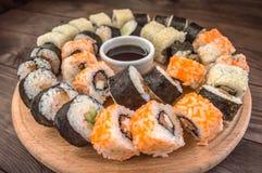 Gesetzter Sashimi und Rollen der Sushi auf einem hölzernen Brett Hintergrund Lizenzfreie Stockfotografie