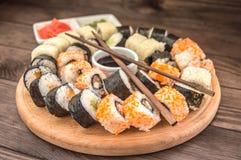 Gesetzter Sashimi und Rollen der Sushi auf einem hölzernen Brett Hintergrund Lizenzfreie Stockfotos