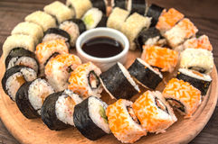 Gesetzter Sashimi und Rollen der Sushi auf einem hölzernen Brett Hintergrund Stockbilder