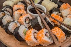 Gesetzter Sashimi und Rollen der Sushi auf einem hölzernen Brett Hintergrund Stockbild