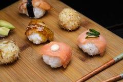 Gesetzter Sashimi und Rollen der Sushi dienten auf hölzernem Schreibtisch Lizenzfreies Stockfoto