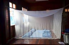 Gesetztes im altem Stil Schlafzimmer- und Indigoschlafens mit Bettnetzen im Haus lizenzfreies stockfoto