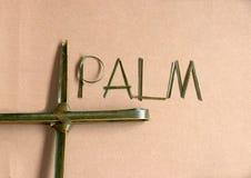 """Gesetztes Kreuz des Palmblattes zum Kruzifix mit dem Palmblatt eingestellt auf das Wort """"palm† auf dem Hintergrund des braun stockbild"""