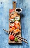 Gesetztes nigiri und Rollen der Sushi auf hölzerner Umhüllung verschalen Lizenzfreie Stockbilder