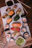 Gesetztes nigiri und Rollen der Sushi dienten auf braunem Holztisch auf marbel Steinplatte Draufsichtlebensmittelphotographie Lizenzfreie Stockbilder