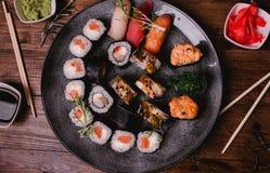 Gesetztes nigiri und Rollen der Sushi dienten auf braunem Holztischhintergrund Draufsichtlebensmittelphotographie Lizenzfreie Stockfotos