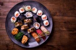 Gesetztes nigiri und Rollen der Sushi dienten auf braunem Holztischhintergrund Draufsichtlebensmittelphotographie Copyspace für T Stockbild