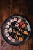 Gesetztes nigiri und Rollen der Sushi dienten auf braunem Holztischhintergrund Draufsichtlebensmittelphotographie Copyspace für T Lizenzfreie Stockbilder