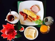 Gesetztes Omelett und Saft des Frühstücks auf schwarzem Hintergrund Stockfotos