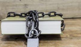 Gesichertes Buch mit Kette auf einem hölzernen Hintergrund Stockbild