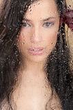 Gesicht der Frau hinter Glas voll der Wassertropfen Lizenzfreies Stockbild