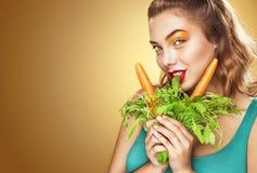 Gesicht der Frau Schöne blonde junge Frau, die den Spaß isst vegetarisches Lebensmittel - Karotte hat Lizenzfreies Stockfoto
