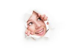Gesicht der Frau spähend durch ein Loch zerrissen im Weißbuchplakat Stockfotos