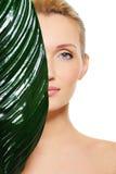 Gesicht der Frau versteckend hinter dem großen grünen Blatt Stockfoto