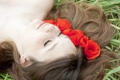 Gesicht der jungen Frau in den Blumen Stockfotografie