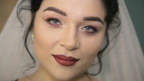 Gesicht der jungen schönen Braut unter dem weißen Hochzeitsschleier stock footage