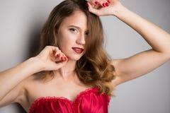 Gesicht der jungen schönen Brunettefrau auf dunklem Hintergrund im Rot Stockbilder