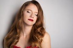 Gesicht der jungen schönen Brunettefrau auf dunklem Hintergrund im Rot Lizenzfreies Stockbild