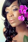 Gesicht der schönen Frau mit Orchideeblumen Lizenzfreies Stockfoto