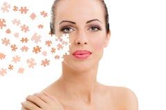 Gesicht der schönen jungen Frau mit einer Puzzlespielcollage ihrer Haut Stockbild