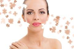 Gesicht der schönen jungen Frau mit einer Puzzlespielcollage ihrer Haut Lizenzfreie Stockfotografie