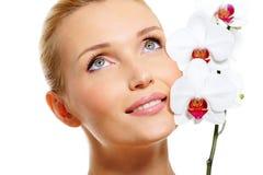 Gesicht der schönen lächelnden Frau mit weißer Orchidee Lizenzfreies Stockfoto