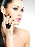Gesicht der schönen Frau mit schwarzen Nägeln und den rosa Lippen Stockbild