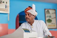 Gesicht des älteren indischen Kellners des populären indischen Cafés mit buntem Innenraum Lizenzfreie Stockbilder