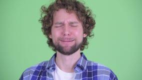 Gesicht des betonten jungen bärtigen Hippie-Mannes, der traurig schreit und schaut stock footage