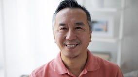 Gesicht des glücklichen lächelnden asiatischen Mannes zu Hause stock footage