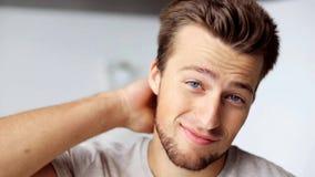 Gesicht des glücklichen lächelnden rührenden Haares des jungen Mannes stock video